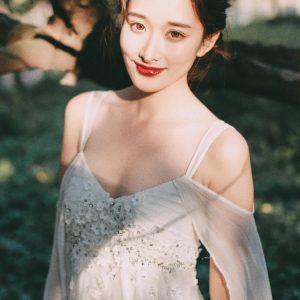 气质美女白色纱裙精致盘发阳光投影写真图片